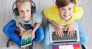 Dečak i devojčica sede na podu i nasmejani koriste slušalice, tablet i laptop