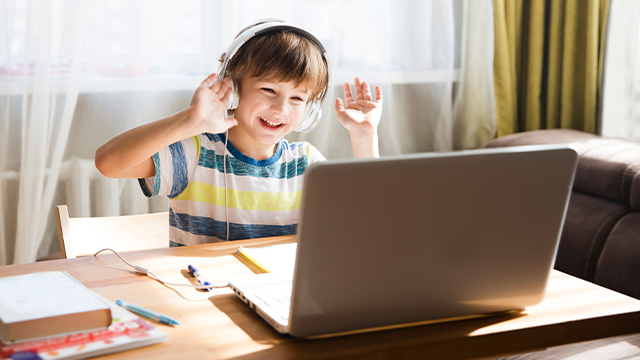 Nasmejan dečak sa slušalicama na ušima sedi za stolom ispred laptopa i veselo maše