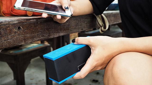 Devojka sa crnim lakom na noktima sedi na klupi u jednoj ruci drži telefon, a u drugoj bluetooth plavo-crni bežični zvučnik koji povezuje sa svojim telefonom