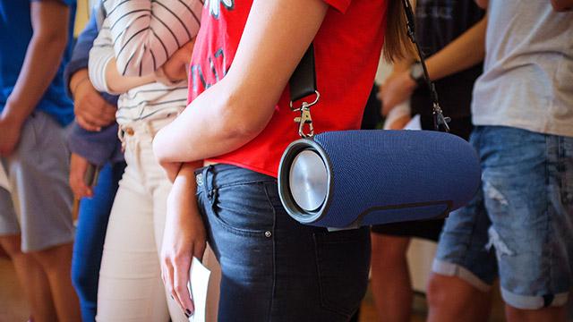 Devojka stoji sa društvom u redu i na ramenu nosi okačen plavi bluetooth zvučnik sa velikim crnim kaišem