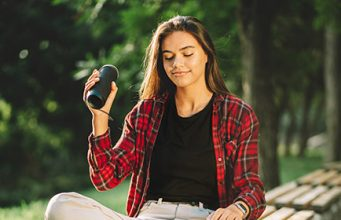 Dugokosa brineta u kariranoj crvenoj košulji sedi na klupi u parku i u ruci drži bluetooth zvučnik