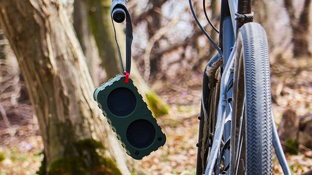 Lako prenosivi bluetooth zvučnik okačen je na gidon od bicikle koja je parkirana u šumi