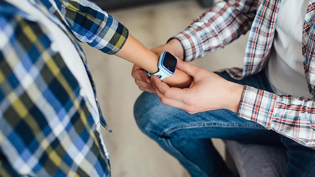 Otac stavlja pametni sat za decu slinu na zglob dok ga ispraća u školu