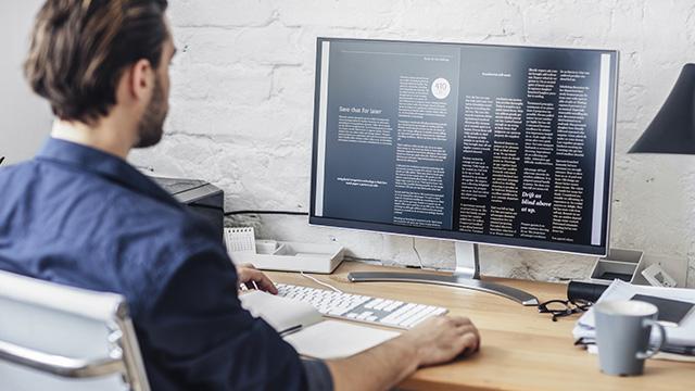 Mladić sedi za stolom i koristi desktop računar za učenje