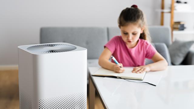 Devojčica u roze majici sedi za stolom i radi domaći, pored nje postavljen je prečišćivač vazduha za bolju koncentraciju tokom rada