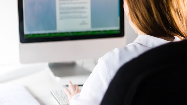 Devojka okrenuta leđima radi na Word dokumentu za računarom