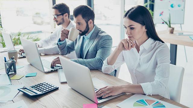 Dva muškarca i žena u kancelariji rade za laptop računarima