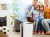 Srećna porodica sa dvoje dece upravo se uselila u kuću, sedi na kauču i uključuje prečišćivač vazduha