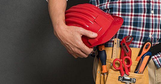 Čovek drži šlem u ruci, a oko struka komplet alata u torbici za alat