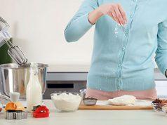 Žena sprema poslastice za slavu na radnom delu u kuhinji, pored nje je mikser sa posudom